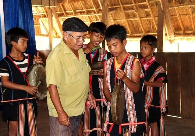 Nghệ nhân A Jin Den, thôn 5, xã Tân Lập đang truyền dạy cồng chiêng cho các cháu